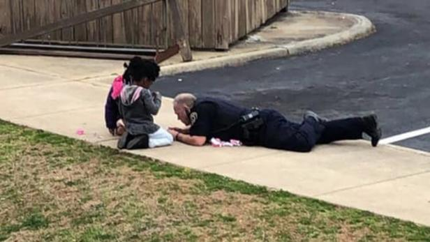 Police Officer C.B. Fleming playing with dolls [WKTR video/screenshot]