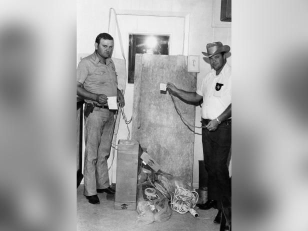 San Augustine County Sheriff deputies Robert McCroskey and Charles Martin display torture implements found inside and under a cabin owned by the parents of Dean Corll [AP Photo]