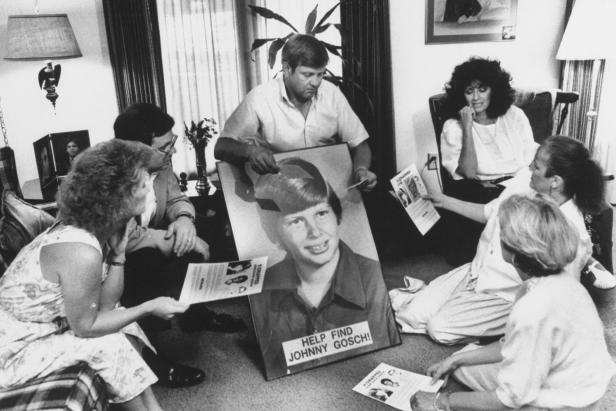 Noreen Gosch sitting next to husband, who is holding poster of their son, Johnny [Taro Yamasaki/The LIFE Images Collection via Getty Images/Getty Images]