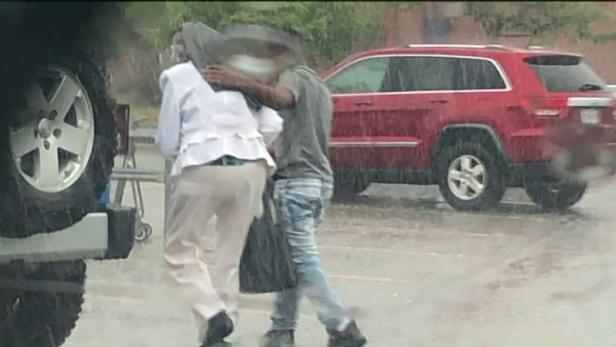 Tyrea helping shield woman from rain [Independence Police Department]